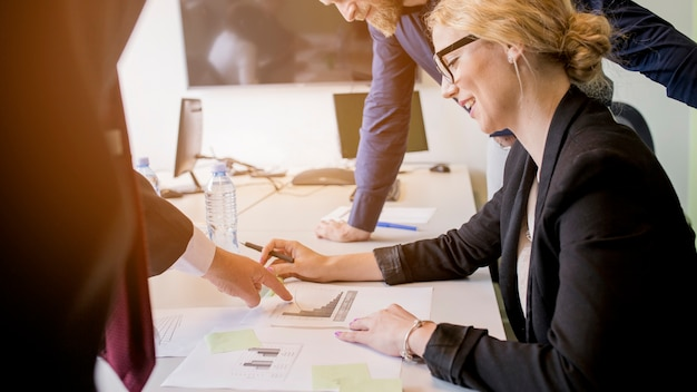 Uśmiechnięta młoda kobieta patrzeje wykres wskazującego jej kolegą na stole Darmowe Zdjęcia