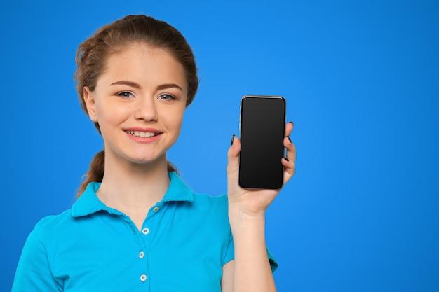Uśmiechnięta Młoda Kobieta Pokazuje Pustego Smartphone Ekran Premium Zdjęcia