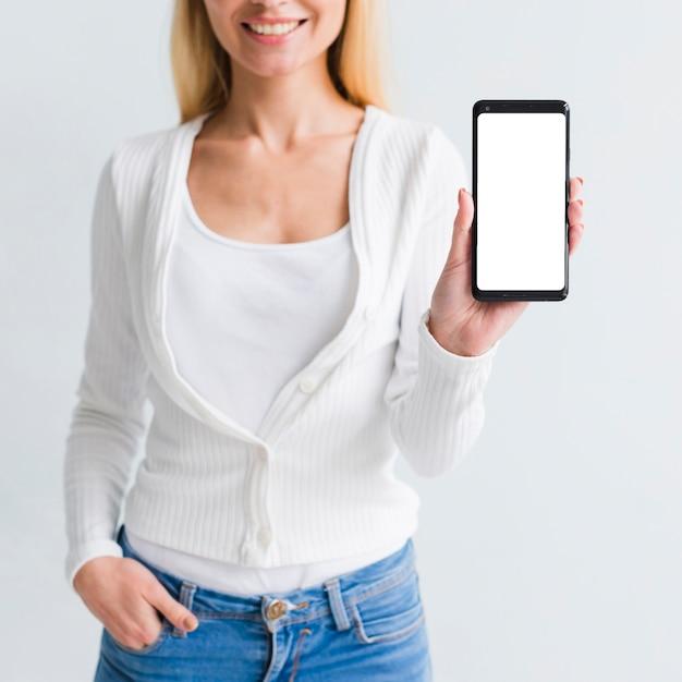 Uśmiechnięta Młoda Kobieta Pokazuje Smartphone Darmowe Zdjęcia