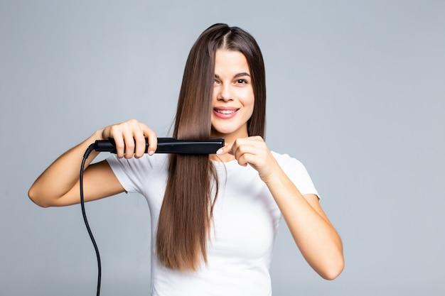 Uśmiechnięta Młoda Kobieta Prostuje Jej Włosy Z Bielem Darmowe Zdjęcia