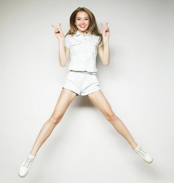 Uśmiechnięta Młoda Kobieta Skoki W Powietrzu Premium Zdjęcia