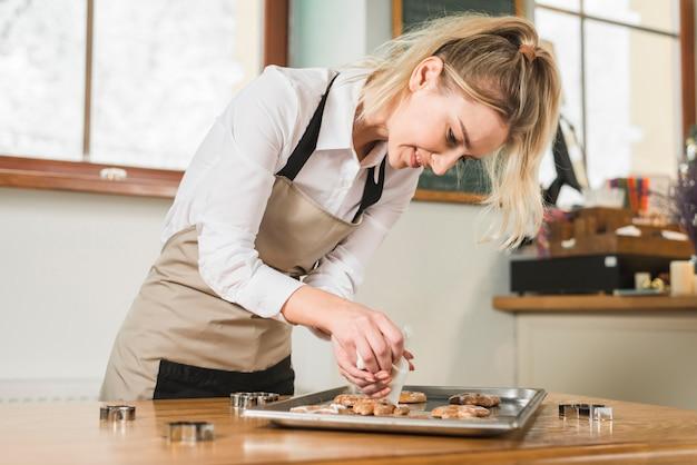 Uśmiechnięta Młoda Kobieta Stosuje śmietankę Nad Piec Ciastkami Na Wypiekowej Tacy Darmowe Zdjęcia
