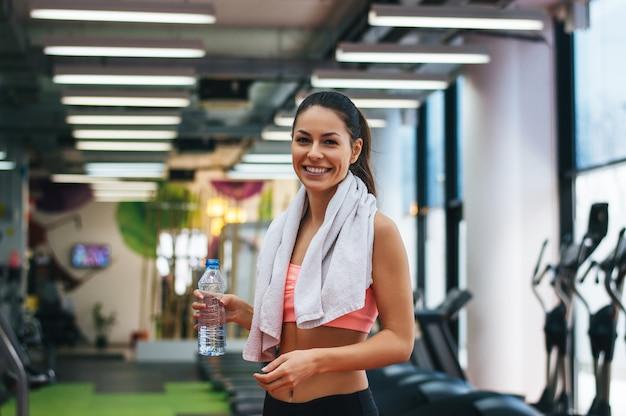 Uśmiechnięta Młoda Kobieta Trzyma Butelkę Z Wodą W Siłowni. Premium Zdjęcia