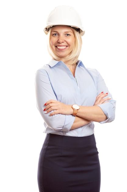 Uśmiechnięta Młoda Kobieta W Biurze Ubrania I Hełm Budowy Na Głowie. Pionowy Premium Zdjęcia