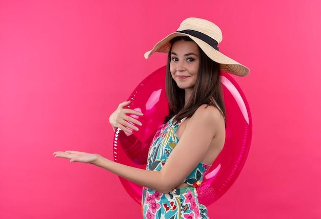 Uśmiechnięta Młoda Kobieta W Kapeluszu, Trzymając Pierścień Do Pływania I Wskazując Ręką Po Lewej Stronie Na Na Białym Tle Różowej ścianie Darmowe Zdjęcia