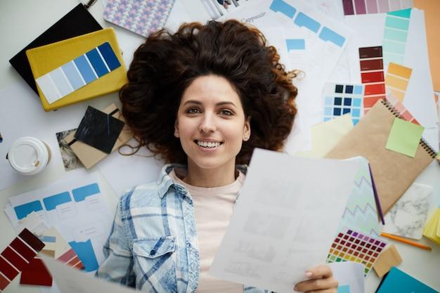 Uśmiechnięta Młoda Kobieta W Kreatywnych Bałagan Premium Zdjęcia