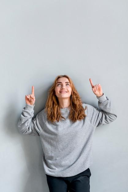 Uśmiechnięta młoda kobieta wskazuje jej palce w górę przyglądającego up przeciw popielatej ścianie Darmowe Zdjęcia