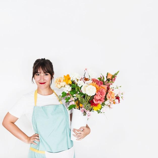 Uśmiechnięta młoda kobieta z kwiat wazą na białym tle Darmowe Zdjęcia