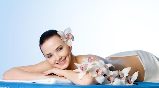 Uśmiechnięta Młoda Kobieta Z Kwiatami Odpoczywa W Salonie Spa Przed Masażem Darmowe Zdjęcia