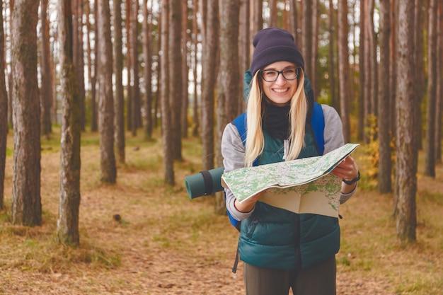 Uśmiechnięta młoda kobieta z podróży mapą i plecakiem w sosnowym lesie Premium Zdjęcia
