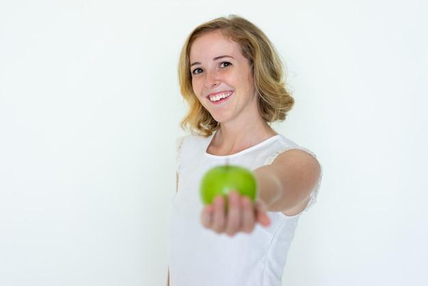 Uśmiechnięta Młoda ładna Kobieta Oferuje Niewyraźne Zielone Jabłko Darmowe Zdjęcia