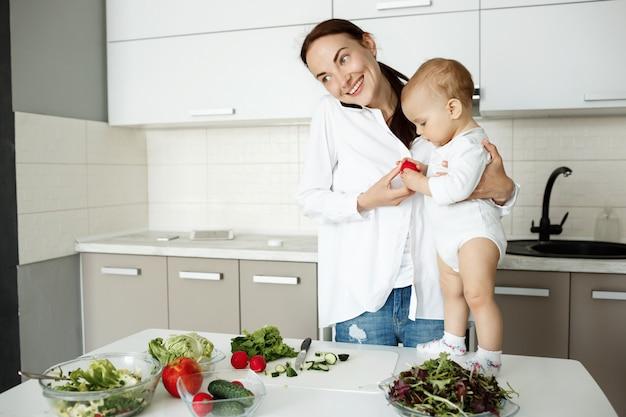 Uśmiechnięta Młoda Matka Trzyma Dziecko, Rozmawia Przez Telefon I Przygotowuje Zdrowe śniadanie Darmowe Zdjęcia
