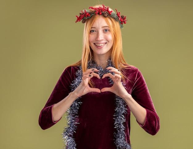 Uśmiechnięta Młoda Piękna Dziewczyna Ubrana W Czerwoną Sukienkę Z Wieńcem I Girlandą Na Szyi Pokazując Gest Serca Na Białym Tle Na Oliwkowym Tle Darmowe Zdjęcia