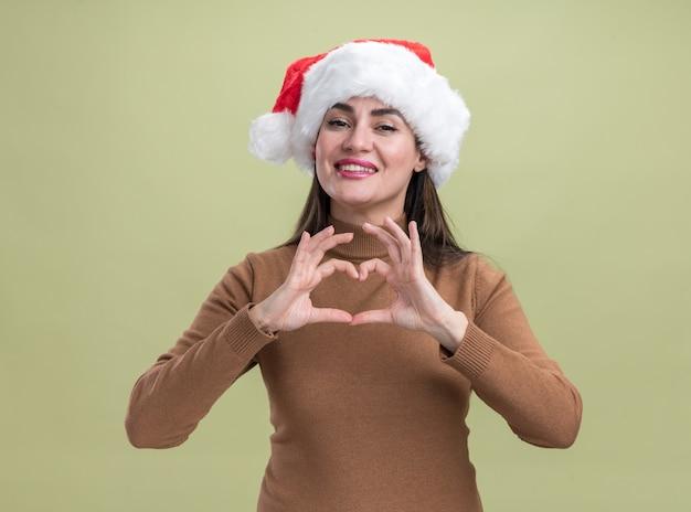 Uśmiechnięta Młoda Piękna Dziewczyna Ubrana W świąteczny Kapelusz Pokazujący Gest Serca Na Oliwkowym Tle Darmowe Zdjęcia