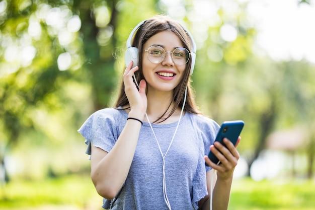 Uśmiechnięta Młoda Studentka Z Plecakiem Trzymając Telefon Komórkowy, Spacery Po Parku, Słuchanie Muzyki W Słuchawkach Darmowe Zdjęcia