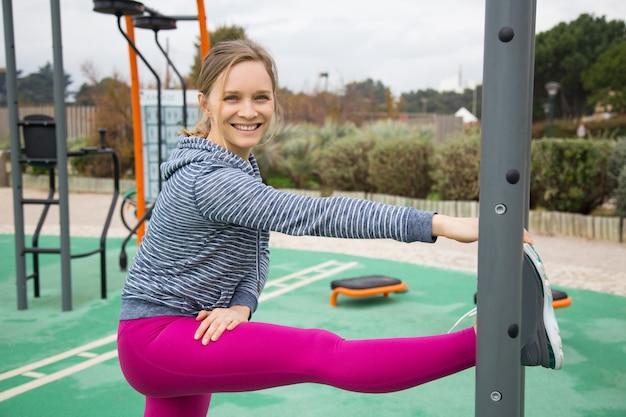 Uśmiechnięta młodej kobiety rozciągania noga na sportach gruntuje Darmowe Zdjęcia