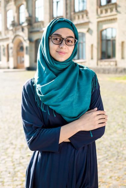 Uśmiechnięta Muzułmańska Młoda Biznesowa Kobieta W Hijab. Szczęśliwy Arabski Dziewczyna Uczeń Z Szkłami. Piękna Islamska Kobieta. Premium Zdjęcia