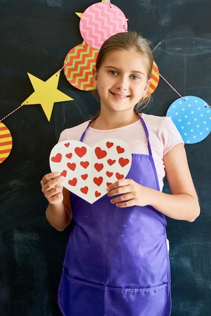 Uśmiechnięta Nastolatka Gospodarstwa Serca Premium Zdjęcia