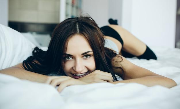 Uśmiechnięta nastolatka leżącego na łóżku Darmowe Zdjęcia