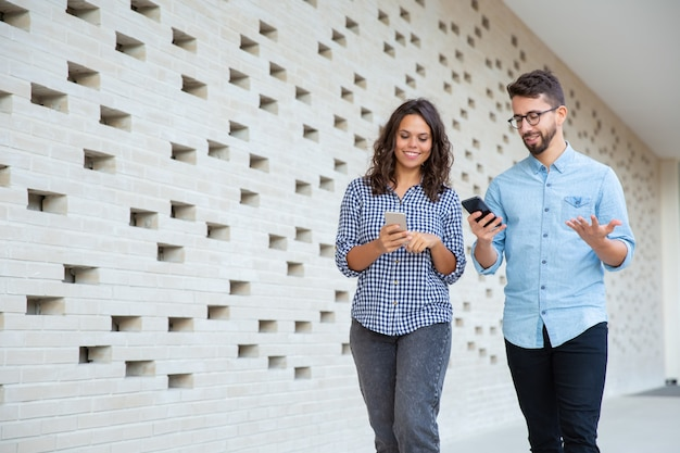 Uśmiechnięta Para Chodzi Smartfony I Używa Darmowe Zdjęcia