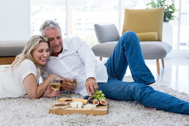 Uśmiechnięta Para Ma Jedzenie Podczas Gdy Kłamający Na Dywaniku Premium Zdjęcia