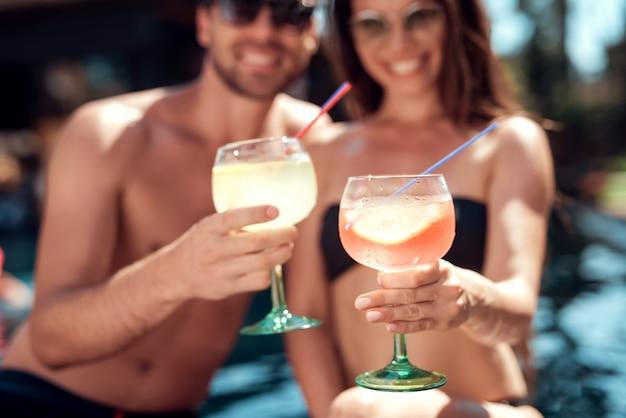 Uśmiechnięta para pije koktajle przy poolside Premium Zdjęcia