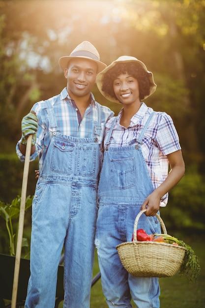 Uśmiechnięta Para W Ogrodowym Mienie świntuchu I Koszu Premium Zdjęcia