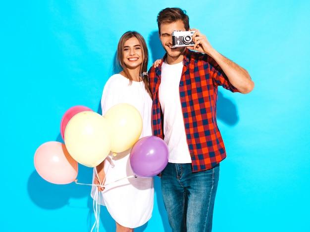 Uśmiechnięta Piękna Dziewczyna I Jej Przystojny Chłopak Trzyma Bukiet Kolorowych Balonów. Szczęśliwa Para Bierze Fotografię One Na Retro Kamerze. Wszystkiego Najlepszego Darmowe Zdjęcia