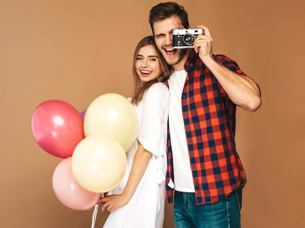 Uśmiechnięta Piękna Dziewczyna I Jej Przystojny Chłopak Trzyma Bukiet Kolorowych Balonów. Szczęśliwa Para Bierze Fotografię One. Wszystkiego Najlepszego Darmowe Zdjęcia