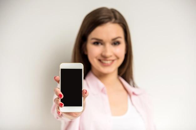 Uśmiechnięta piękna dziewczyna pokazuje pustego mądrze telefonu ekran. Premium Zdjęcia
