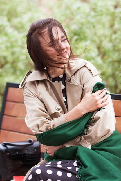 Uśmiechnięta Piękna Dziewczyna Siedzi W Parku Miejskim Na ławce. Wiatr Rozwijający Długie Włosy Szczęśliwej Młodej Kobiety. Premium Zdjęcia