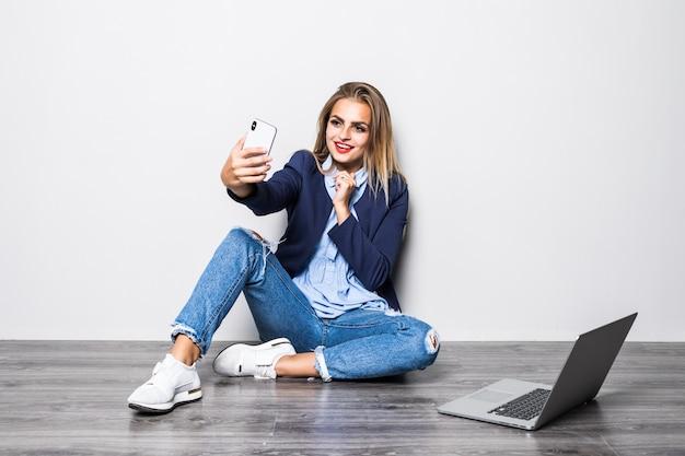 Uśmiechnięta Piękna Dziewczyna Studentka Siedzi Na Podłodze Z Białą ścianą I Rozmowy Wideo Na Telefon Komórkowy Z Happy, Gdy Ona Używa Badania Komputera Przenośnego. Darmowe Zdjęcia