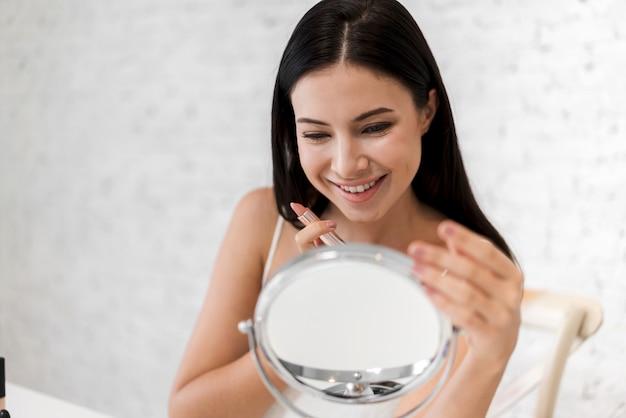Uśmiechnięta Piękna Kobieta świeża Zdrowa Skóra Patrzeje Na Lustrze I Stosuje Pomadkę Premium Zdjęcia