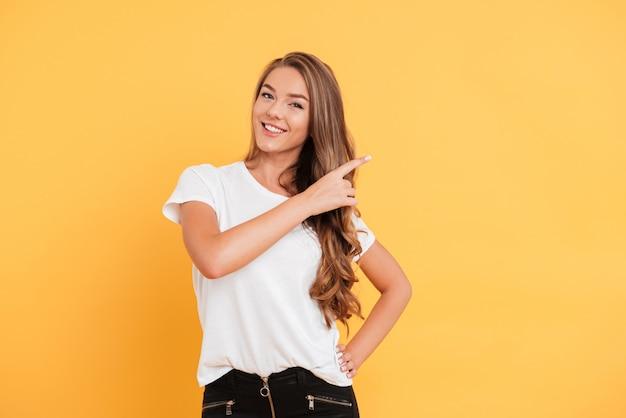 Uśmiechnięta Piękna Młoda Kobieta Wskazuje Copyspace. Darmowe Zdjęcia