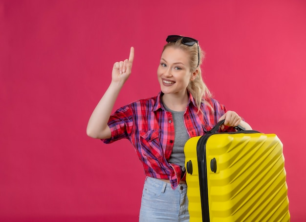 Uśmiechnięta Podróżnik Młoda Dziewczyna Ubrana W Czerwoną Koszulę I Okulary Na Głowie Trzymając Walizkę Wskazuje Do Góry Na Na Białym Tle Różowym Darmowe Zdjęcia