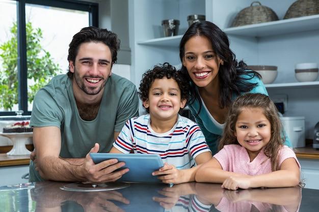 Uśmiechnięta rodzina używa pastylkę w kuchni Premium Zdjęcia