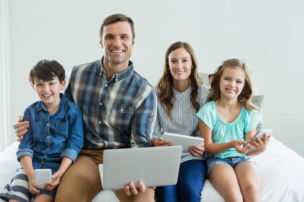 Uśmiechnięta Rodzina Za Pomocą Laptopa, Cyfrowego Tabletu I Telefonu Komórkowego W Sypialni Premium Zdjęcia
