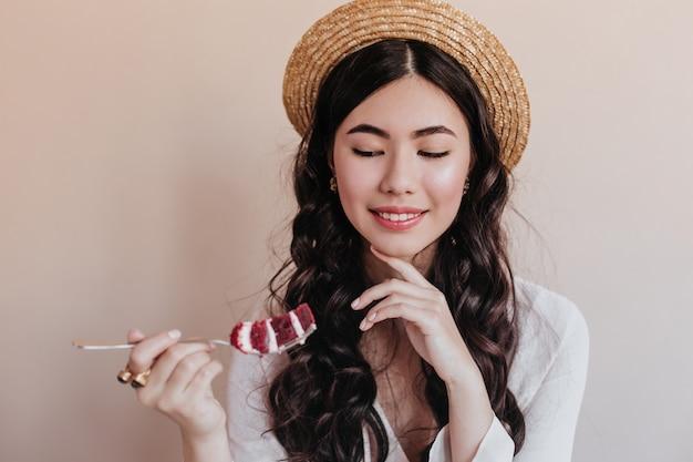Uśmiechnięta Romantyczna Azjatycka Kobieta Jedzenie Ciasta. Elegancka Kobieta Kręcone, Ciesząc Się Deserem. Darmowe Zdjęcia