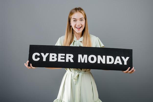 Uśmiechnięta rozochocona blondynki dziewczyna z cyber poniedziałku znakiem odizolowywającym nad popielatym Premium Zdjęcia