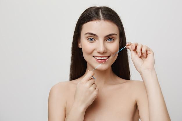 Uśmiechnięta śliczna Kobieta Czyści Zęby Nicią Dentystyczną Darmowe Zdjęcia