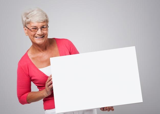 Uśmiechnięta Starsza Kobieta Trzyma Białą Tablicę Darmowe Zdjęcia