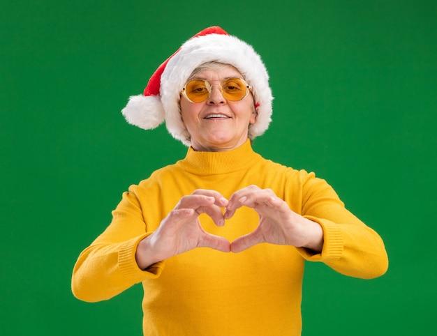 Uśmiechnięta Starsza Kobieta W Okularach Przeciwsłonecznych Z Santa Hat Gestów Znak Serca Na Białym Tle Na Zielonym Tle Z Miejsca Na Kopię Darmowe Zdjęcia