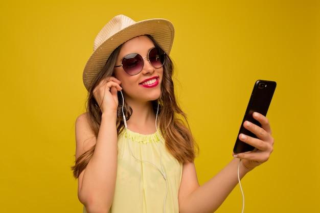 Uśmiechnięta Szczęśliwa Kobieta W Letnim Kapeluszu I Okularach Przeciwsłonecznych Z Smartphone Darmowe Zdjęcia