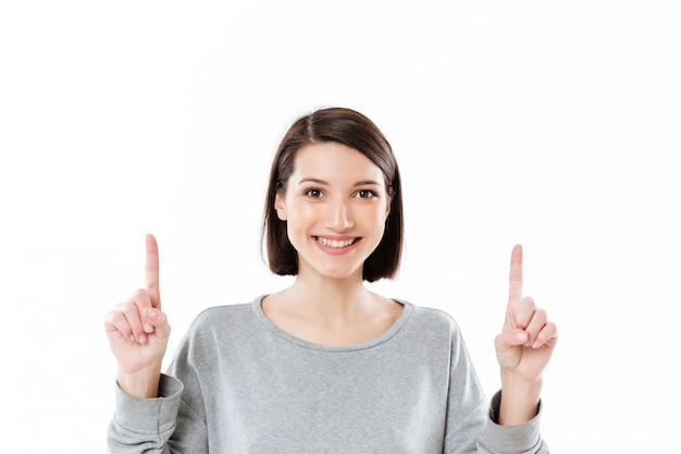Uśmiechnięta Szczęśliwa Kobieta Wskazuje Dwa Palca Up Przy Kopii Przestrzenią Darmowe Zdjęcia