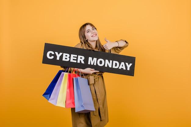 Uśmiechnięta szczęśliwa kobieta z cyber poniedziałku znakiem i kolorowymi torba na zakupy odizolowywającymi nad kolorem żółtym Premium Zdjęcia