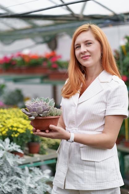 Uśmiechnięta Szczęśliwa Kwiaciarka W Swoim Przedszkolu Stojąca, Trzymając W Rękach Doniczkową Kombinację Sukulentów, Gdy Zajmuje Się Roślinami Ogrodowymi W Szklarni Darmowe Zdjęcia