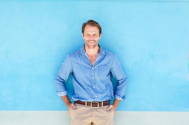 Uśmiechnięta ufna mężczyzna pozycja przeciw błękit ścianie Premium Zdjęcia