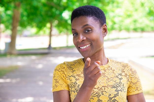 Uśmiechnięta ufna murzynka wskazuje z palcem przy kamerą Darmowe Zdjęcia