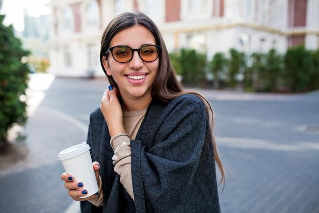 Uśmiechnięta Urocza Nieśmiała Kobieta Spaceru Z Kawą Na Ulicy I Cieszy Się Weekendem W Mieście Darmowe Zdjęcia