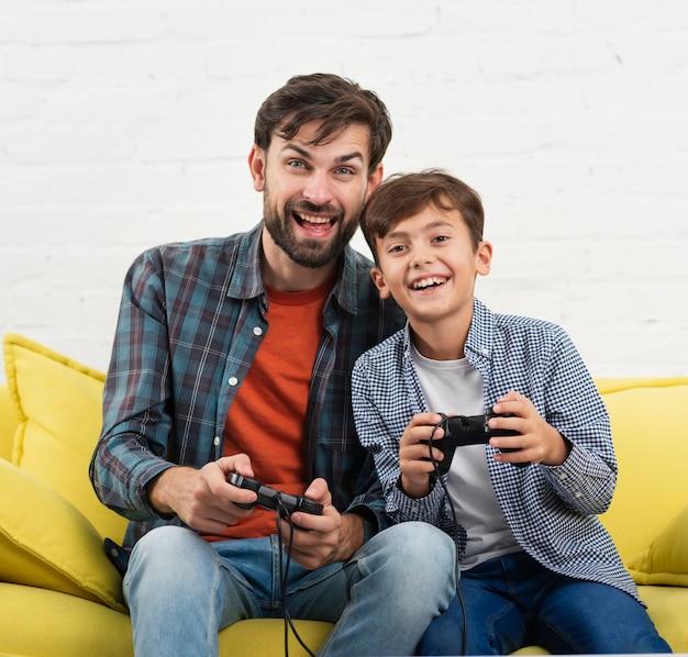 Uśmiechnięte Dziecko I Ojciec Gra Na Konsoli Darmowe Zdjęcia